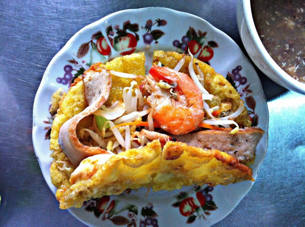 Crisy banh khoai is a pan-fried crepe that is typically stuffed with shrimp and pork belly